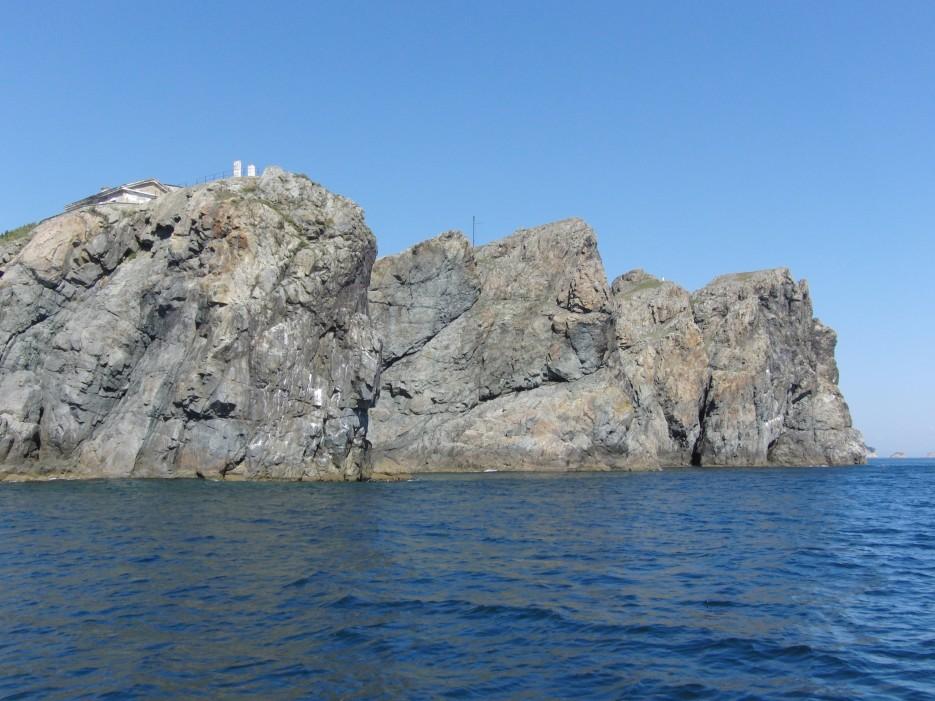 Маяк Гамова. Полуостров Гамова. Хасанский район.   Здесь почти каждое утро загоняют рыбу касатки с моря в б. Опасная. В 1973 г. здесь в трал поймали ската около 2 метров в диаметре (думали, что это манта), в 1979г. именно здесь была выброшена на берег кожистая черепаха, длиной в 2 метра и весом около 200 кг. Недалеко от этого места был пойман на мелководье осьминог в 56 кг. весом. В тёплые года сюда приходят несвойственные нам виды рыб и организмов (до 45 видов). Это акулы, тунцы, ставрида, сайра, скумбрия и даже летучие рыбы.  А теперь информация для любителей понырять.  Возле Маяка было довольно много кораблекрушений. Наиболее известны два из них с судами «Кварц» и «Владимир». Никто из людей не погиб, но «корабли-герои» остались под водой. На их остатках можно понырять. Глубины 19-34. «Кварц», затонул в 1982 году после того, как наткнулся на большой подводный камень. Он лежит на ровном киле и прекрасно сохранился. | Маяк Гамов. Хасанский район.