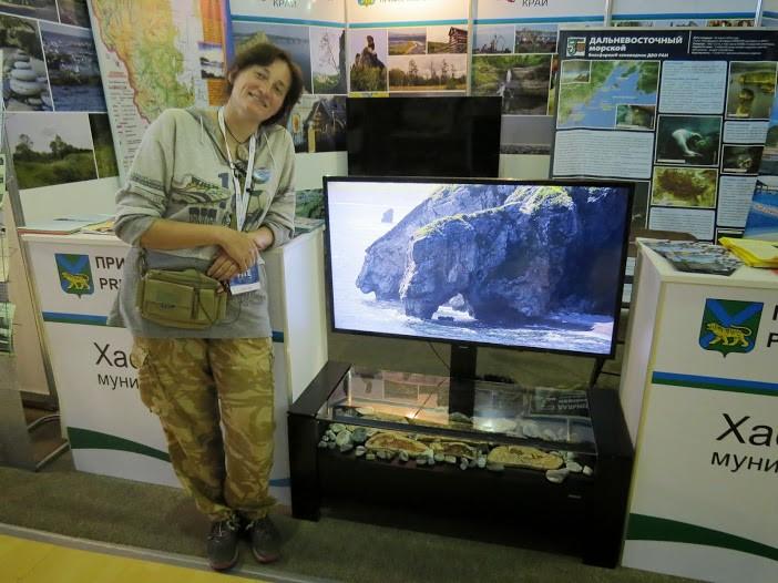 На мониторе - бухта Агатовая. Под монитором - выставка поделок из камня той же бухты. | Хасанский район на туристской выставке на острове Русском