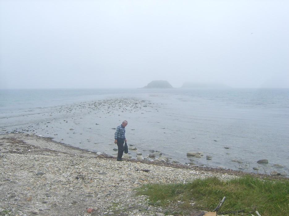 Наш водитель и гид Сергей набирает ракушку на свою фазенду. Здесь еще красивые мраморные окатыши.   Скала Крепость на въезде в Славянку и полуостров Краббе - штурм в тумане