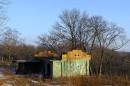 Заброшенные домики, оставшиеся от военных постепенно зарастают травой.